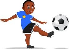 Muchacho negro que golpea el balón de fútbol con el pie Foto de archivo libre de regalías