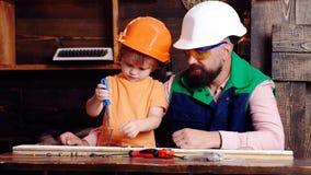 Muchacho, niño ocupado en casco protector aprendiendo torcer los tornillos con un destornillador con el papá Taller y manitas almacen de video