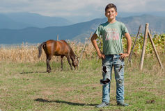 Muchacho no identificado que se divierte en granja de su familia con el caballo y viñedo en valle verde Fotografía de archivo libre de regalías