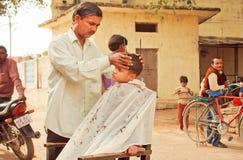 Muchacho no identificado que se sienta en silla de la peluquería de caballeros rural y que hace el nuevo peinado de un peluquero Imagen de archivo libre de regalías