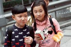 Muchacho no identificado y muchacha que comen los bocados al aire libre en la manera de la escuela Foto de archivo libre de regalías