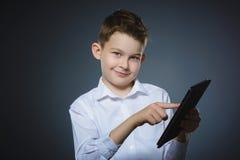 Muchacho o adolescente joven sonriente con el ordenador de la PC de la tableta Imagenes de archivo