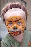 Muchacho o niño joven cubierto en pintura de la cara del tigre Imagenes de archivo