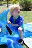 Muchacho o niño joven que se sienta en delfín inflable por la piscina Foto de archivo libre de regalías