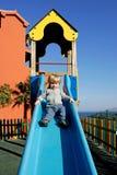 Muchacho o niño joven que viene abajo una diapositiva en el sol Fotos de archivo libres de regalías