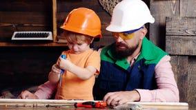 Muchacho ocupado en el casco protector que aprende torcer los tornillos con destornillador con el pap? Concepto del taller y de l metrajes