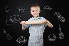 Muchacho optimista que usa un rodillo mientras que cocina las empanadas para su madre Imagen de archivo libre de regalías