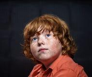 Muchacho pecoso del rojo-pelo que presenta en fondo oscuro. Imagenes de archivo
