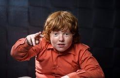 Muchacho pecoso del rojo-pelo que presenta en fondo oscuro. Foto de archivo libre de regalías