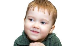 Muchacho pelirrojo con una mirada astuta al lado en un fondo blanco fotografía de archivo libre de regalías