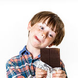 Muchacho pelirrojo feliz con la barra de chocolate Imagen de archivo