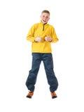 Muchacho pelirrojo joven en un muchacho de salto de la chaqueta amarilla con las manos apretadas en un puño y aumentadas su pulga Foto de archivo libre de regalías