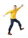 Muchacho pelirrojo joven en una chaqueta amarilla que salta con los brazos extendidos Fotografía de archivo libre de regalías