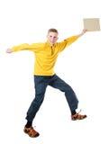 Muchacho pelirrojo joven en una chaqueta amarilla que salta con los brazos extendidos y los controles en su placa de la mano Imagen de archivo
