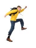 Muchacho pelirrojo joven en una chaqueta amarilla y un muchacho de la mochila que salta con los brazos extendidos Foto de archivo libre de regalías