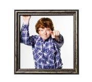 Muchacho pelirrojo que presenta con el marco Fotos de archivo libres de regalías