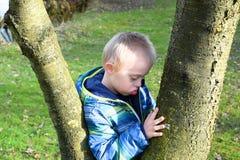 Muchacho pensativo con síndrome abajo quién abraza árboles Imagen de archivo