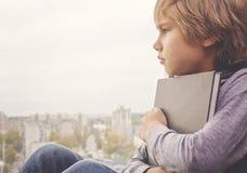 Muchacho pensativo joven con el libro que se sienta y que mira a través de la ventana Fotos de archivo