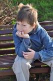Muchacho pensativo que se sienta en un banco de parque Fotografía de archivo