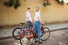 Muchacho pensativo y muchacha bonita con el pelo rubio que se coloca con las bicicletas rojas y azules y que lleva a cabo las man Fotos de archivo