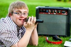 Muchacho perjudicado que canta con el micrófono y el amplificador Imágenes de archivo libres de regalías
