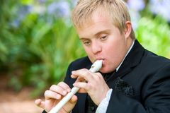 Muchacho perjudicado que toca la flauta del bloque. Foto de archivo libre de regalías