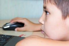 muchacho a pesar de juegos de la fatiga en el ordenador Imagenes de archivo
