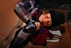 Muchacho pobre del mendigo que se prepara para dormir en la calle - cubierta con fotos de archivo libres de regalías