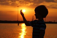 Muchacho por el mar en la puesta del sol Fotos de archivo libres de regalías