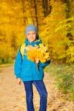 Muchacho positivo con el manojo de hojas de arce amarillas Fotografía de archivo
