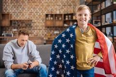 Muchacho pre-adolescente agradable que presenta con la bandera de los E.E.U.U. Imagenes de archivo