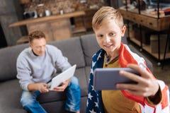 muchacho Pre-adolescente en la bandera de los E.E.U.U. que toma un selfie en sala de estar Fotos de archivo libres de regalías