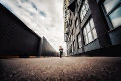 muchacho Pre-adolescente en una calle en una ciudad grande al lado de un edificio alto solamente Fotos de archivo
