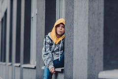 muchacho Pre-adolescente en una calle en una ciudad grande al lado de un edificio alto solamente Imágenes de archivo libres de regalías