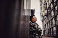 muchacho Pre-adolescente en una calle en una ciudad grande al lado de un edificio alto solamente Fotos de archivo libres de regalías