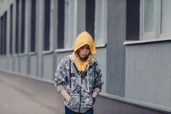 muchacho Pre-adolescente en una calle en una ciudad grande al lado de un edificio alto solamente Imagen de archivo