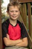 Muchacho pre-adolescente feliz que se sienta afuera Fotografía de archivo libre de regalías