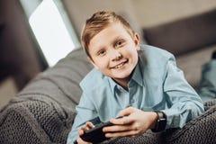Muchacho pre-adolescente lindo que miente en el sofá y que juega a juegos Foto de archivo