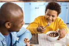 Muchacho pre-adolescente optimista que desayuna con su padre Fotografía de archivo libre de regalías