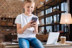 Muchacho pre-adolescente optimista que se sienta en la tabla y amigos que mandan un SMS Imagen de archivo