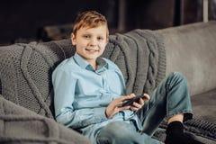 Muchacho pre-adolescente precioso que presenta mientras que juega en el teléfono Foto de archivo libre de regalías