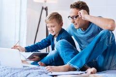 muchacho Pre-adolescente que comparte sus ideas sobre proyecto de la escuela con el padre imagenes de archivo