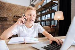muchacho Pre-adolescente que habla en el teléfono mientras que usa el ordenador portátil Fotos de archivo