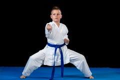muchacho Pre-adolescente que hace karate en un fondo negro Fotografía de archivo