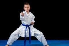 muchacho Pre-adolescente que hace karate en un fondo negro Foto de archivo
