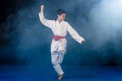 muchacho Pre-adolescente que hace karate en un fondo negro con humo Fotografía de archivo libre de regalías