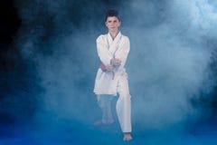 muchacho Pre-adolescente que hace karate en un fondo negro con humo Fotos de archivo libres de regalías