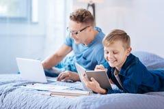 muchacho Pre-adolescente que hace la preparación de la matemáticas mientras que su funcionamiento del padre Imágenes de archivo libres de regalías