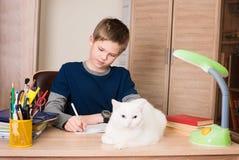 muchacho Pre-adolescente que hace su preparación en casa en su sitio con c blanca Fotos de archivo