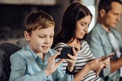 muchacho Pre-adolescente que juega en el teléfono al lado de sus padres Fotos de archivo libres de regalías
